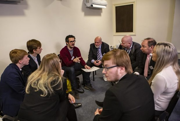 9 security professionals gathered around discussing ideas during a workshop.